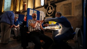 A man recieves his Pfizer-BioNTech vaccination inside Salisbury Cathedral in Salisbury, England, Wednesday, Jan. 20, 2021. Salisbury Cathedral opened its doors for the second time as a venue for the Sarum South Primary Care Network COVID-19 Local Vaccination Service. (AP Photo/Frank Augstein)