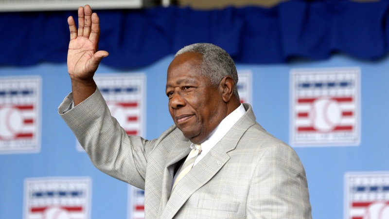 FILE - Hall of Famer Hank Aaron waves to the crowd during Baseball Hall of Fame induction ceremonies in Cooperstown, N.Y., in this Sunday, July 28, 2013, file photo. Hank Aaron, who endured racist threats with stoic dignity during his pursuit of Babe Ruth but went on to break the career home run record in the pre-steroids era, died early Friday, Jan. 22, 2021. He was 86. The Atlanta Braves said Aaron died peacefully in his sleep. No cause of death was given. (AP Photo/Mike Groll, File)