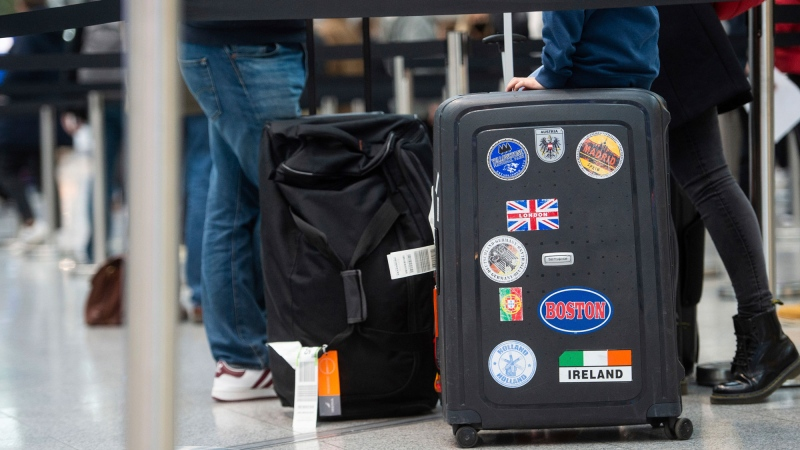 "A family queues with their luggage at the airport in Duesseldorf, Germany, for a Corona test, while a British flag with the words ""London"" can be seen on the suitcase on Monday, Dec. 21, 2020. Due to the emergence of a new, supposedly more contagious variant of the virus in the south-east of England, flights from the UK have been grounded as of today, although flights to the UK are continuing. (Jonas Guettler/dpa via AP)"