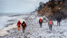Members of a ground search and rescue team walk along the shore of the Bay of Fundy in Hillsburn, N.S. as they continue to look for five fishermen missing after the scallop dragger Chief William Saulis sank in the Bay of Fundy, on Wednesday, Dec. 16, 2020. RCAF search and rescue aircraft and Canadian Coast Guard boats have been dispatched as well. THE CANADIAN PRESS/Andrew Vaughan