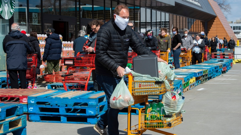 Long lines of masked shoppers wait to shop for groceries in Toronto on Thursday, April 9, 2020. THE CANADIAN PRESS/Frank Gunn