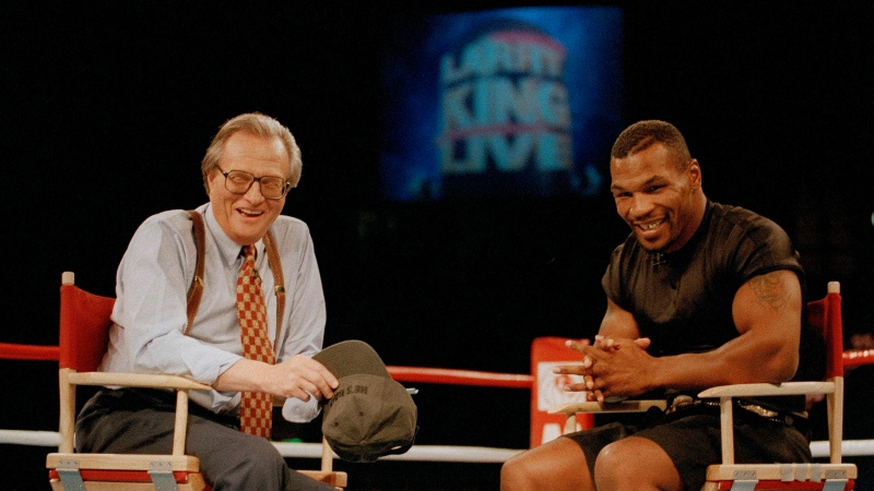 "In this Aug. 16, 1995 file photo, former heavyweight champion Mike Tyson, right, shares a laugh with TV talk show host Larry King during the broadcasting of the ""Larry King Live"" show from inside the ring at the MGM Grand Gardens in Las Vegas. King, who interviewed presidents, movie stars and ordinary Joes during a half-century in broadcasting, has died at age 87. Ora Media, the studio and network he co-founded, tweeted that King died Saturday, Jan. 23, 2021 morning at Cedars-Sinai Medical Center in Los Angeles."