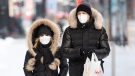 People wear face masks as they walk along a street in Montreal, Saturday, January 23, 2021, as the COVID-19 pandemic continues in Canada and around the world. THE CANADIAN PRESS/Graham Hughes