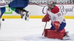 Montreal Canadiens goalie Carey Price makes the save as Vancouver Canucks' Brock Boeser jumps in front of him during the second period of an NHL hockey game in Vancouver, on Saturday, January 23, 2021. THE CANADIAN PRESS/Darryl Dyck