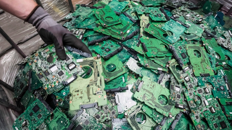 In this photo taken on July 13, 2018, a worker throws components of electronic elements into a bin at the Out Of Use company warehouse in Beringen, Belgium. (AP Photo/Geert Vanden Wijngaert)
