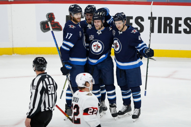 Winnipeg Jets' Adam Lowry (17) , Andrew Copp (9), Nikolaj Ehlers (27) and Neal Pionk (4) celebrates Ehlers' goal against the Ottawa Senators during first period NHL action in Winnipeg on Saturday, January 23, 2021. THE CANADIAN PRESS/John Woods