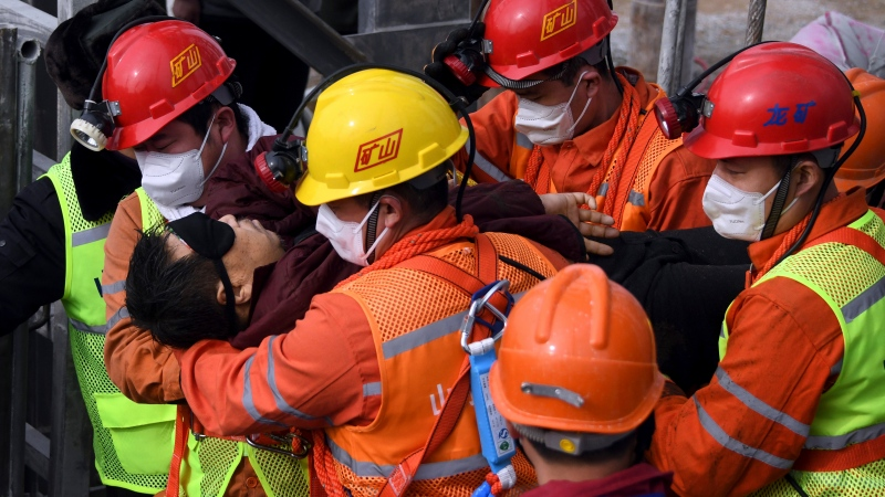 In this photo released by Xinhua News Agency, rescuers carry a miner who was trapped in a mine to an ambulance in Qixia City in east China's Shandong Province, Sunday, Jan. 24, 2021. (Chen Hao/Xinhua via AP)