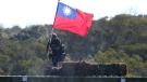 A soldier holds a Taiwan national flag during a military exercise in Hsinchu County, northern Taiwan, Tuesday, Jan. 19, 2021. Taiwanese troops using tanks, mortars and small arms staged a drill Tuesday aimed at repelling an attack from China, which has increased its threats to reclaim the island and its own displays of military might. (AP Photo/Chiang Ying-ying)