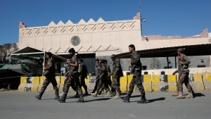 Houthi soldiers walk past the closed U.S. embassy during a demonstration over its decision to designate the Houthis a foreign terrorist organisation in Sanaa, Yemen, Monday, Jan. 18, 2021. (AP Photo/Hani Mohammed)