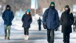 People wear face masks as they walk in the Old Port of Montreal, Saturday, January 23, 2021, as the COVID-19 pandemic continues in Canada and around the world. THE CANADIAN PRESS/Graham Hughes