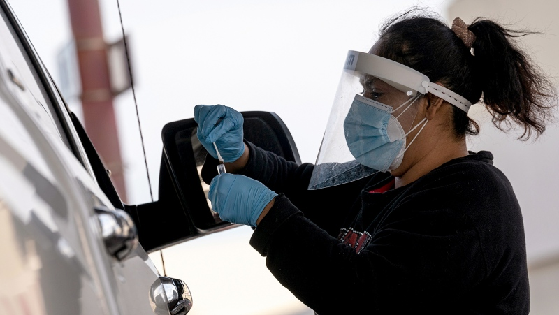 Just over a year since the first reported Covid-19 case in the US, the United States nears 25 million infections. This image shows a healthcare worker running a Covid-19 test inside San Francisco International Airport (SFO) in San Francisco, California, on January 9, 2021. (David Paul Morris/Bloomberg/Getty Images)