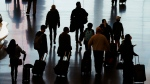 In this Nov. 25, 2020 file photo, travelers walk through the Salt Lake City International Airport in Salt Lake City, a day before Thanksgiving. (AP Photo/Rick Bowmer, File)