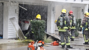 Surrey firefighters attend to a fire in a garage in Surrey, B.C. on Jan. 24, 2021.