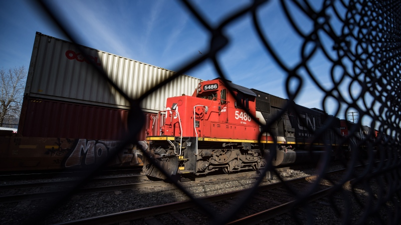 CN Rail locomotives are moved on tracks past cargo containers sitting on idle train cars at port in Vancouver, on Friday, February 21, 2020. (THE CANADIAN PRESS/Darryl Dyck)