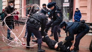 Police officers detain opposition activist Pavel Krysevich, on the ground, after his action in support of Russian opposition leader Alexei Navalny and against the mass arrests at Saturday's uncoordinated rally in Moscow, Russia, Sunday, Jan. 24, 2021. (AP Photo/George Markov)