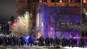 Tacoma Police and other law enforcement officials stand in a line as protesters approach in the street in front of the City-County Building during a protest against police brutality, late Sunday, Jan. 24, 2021, in downtown Tacoma, Wash., south of Seattle. (AP Photo/Ted S. Warren)