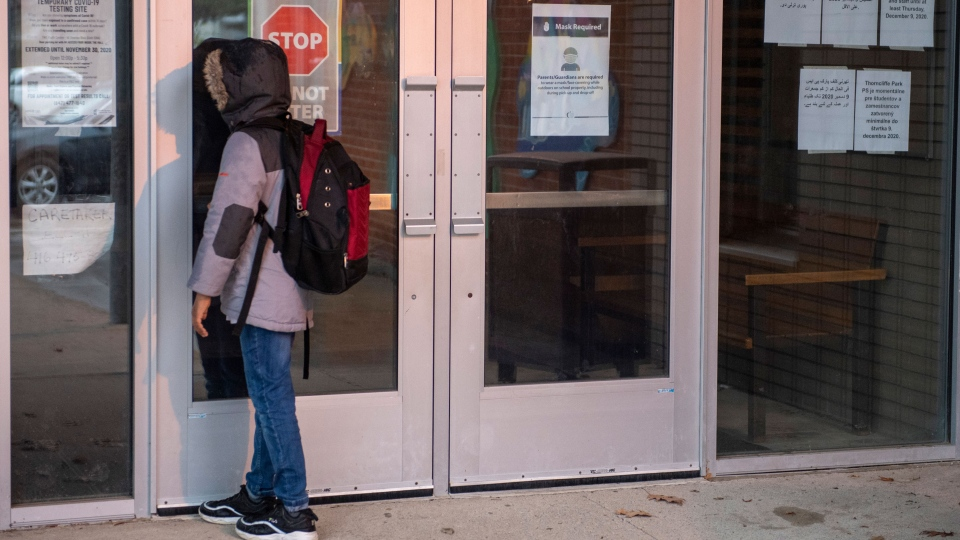 A student peers through the front door of Thorncliffe Park Public School in Toronto on Friday December 4, 2020. Toronto Public Health closed the school due to a COVID19 outbreak. THE CANADIAN PRESS/Frank Gunn