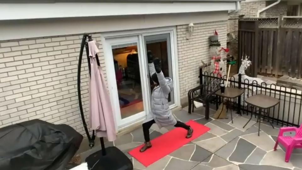 Teacher teaching yoga through windows to keep safe