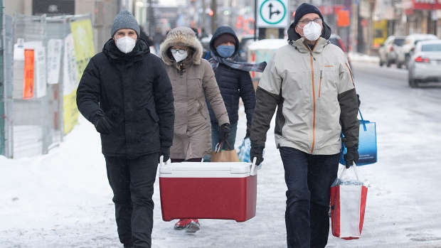 People deliver food and water to members of the homeless community in Montreal, Saturday, January 23, 2021, as the COVID-19 pandemic continues in Canada and around the world. (THE CANADIAN PRESS/Graham Hughes)