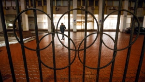 A man walks past a fence with Olympic Rings near the Russian National Olympic Committee building in Moscow, Russia, on Dec. 17, 2020. (Alexander Zemlianichenko / AP)