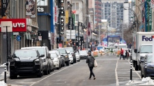 A man crosses a quiet Saint-Catherine Street under Quebec's COVID-19 lockdown in Montreal, on Monday, January 11, 2021. THE CANADIAN PRESS/Paul Chiasson