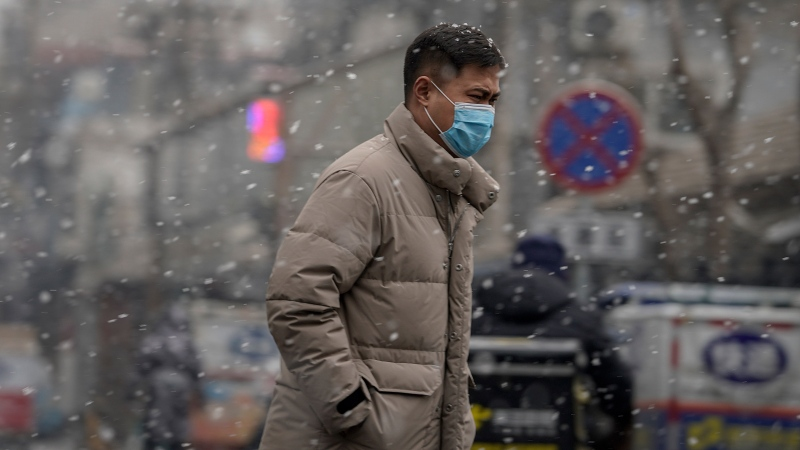 A man wearing a face mask to help curb the spread of the coronavirus walks through falling snowflakes on a street in the morning in Beijing, Monday, Jan. 25, 2021. (AP Photo/Andy Wong)