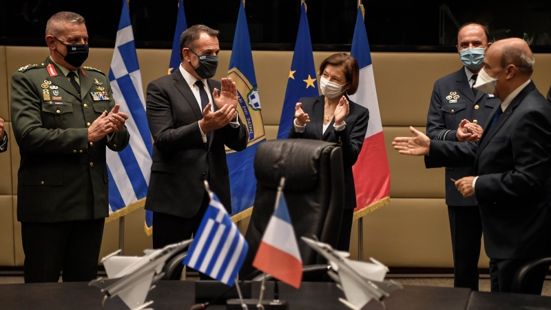 French Defense Minister Florence Parly, center, her Greek counterpart Nikos Panagiotopoulos, second left, and the officials applaud after signing the Rafale warplane deal in Athens, Monday, Jan. 25, 2021. Greece is due to sign a 2.3 billion euro ($2.8 billion) deal with France Monday to purchase 18 Rafale fighter jets to address tension with neighbor Turkey. (Louisa Gouliamaki/Pool via AP)