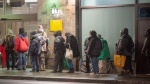 People line-up at a hotel for the homeless before the 8 p.m. COVID-19 curfew Monday, January 11, 2021 in Montreal. THE CANADIAN PRESS/Ryan Remiorz
