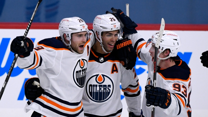 Edmonton Oilers' Leon Draisaitl (29) celebrates his game-winning goal against the Winnipeg Jets with teammates Darnell Nurse (25) and Ryan Nugent-Hopkins (93) during third period NHL action in Winnipeg on Sunday Jan. 24, 2021. THE CANADIAN PRESS/Fred Greenslade