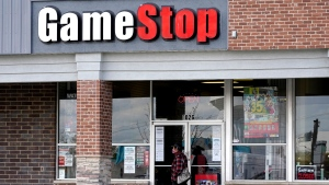 A woman wears a face mask as she walks past a GameStop store in Des Plaines, Ill., Thursday, Oct. 15, 2020. (AP Photo/Nam Y. Huh, file)