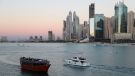 Tourists on a yacht as they pass a traditional dhow serving a dinner cruise, in Dubai, United Arab Emirates, Tuesday, Jan. 12, 2021. (AP Photo/Kamran Jebreili)
