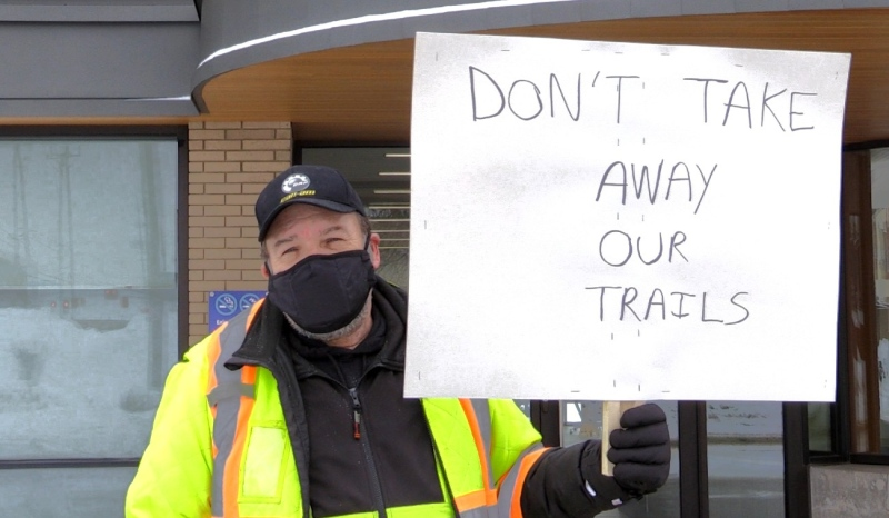 Snowmobiler Steven Godfrey, from Ahmic Harbour, was the lone protestor walking up and down the sidewalk in front of the outside the North Bay Parry Sound District Health Unit for two hours. (Eric Taschner/CTV News)