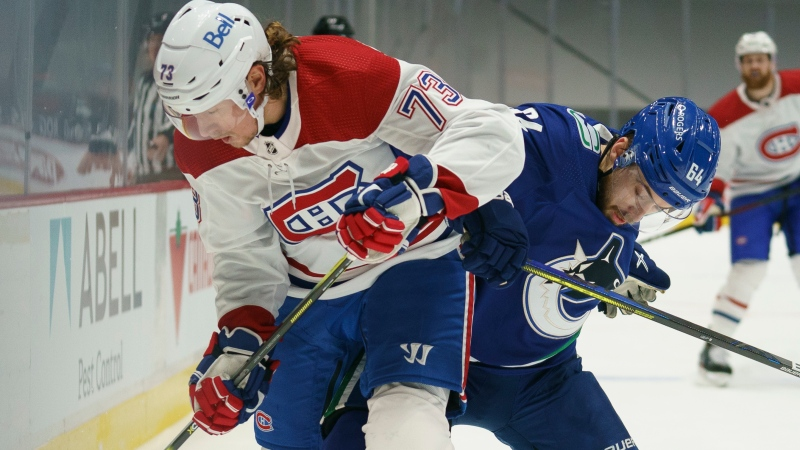 Vancouver Canucks centre Tyler Motte (64) fights for control of the puck with Montreal Canadiens right wing Tyler Toffoli (73) during first period NHL action in Vancouver, Thursday, January 21, 2021. THE CANADIAN PRESS/Jonathan Hayward