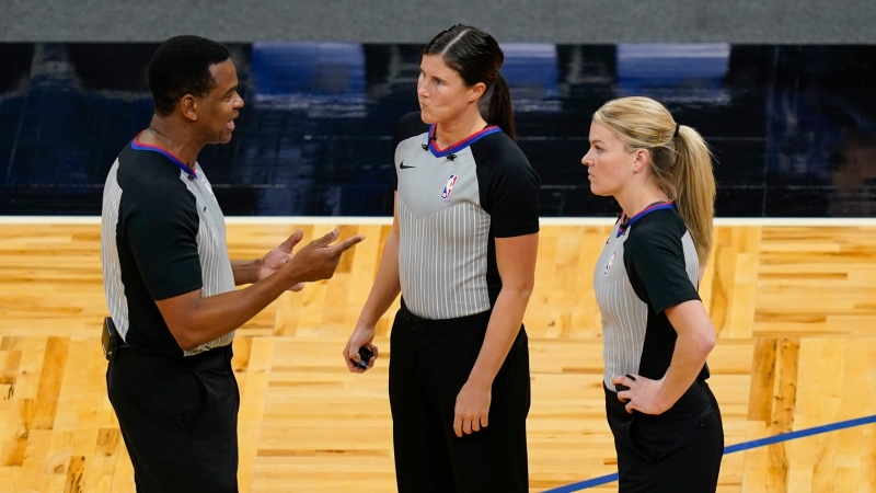 Referees from left, Sean Wright, Natalie Sago and Jenna Schroeder have a discussion during a time out in the second half of an NBA basketball game between the Orlando Magic and the Charlotte Hornets, Monday, Jan. 25, 2021, in Orlando, Fla. (AP Photo/John Raoux)