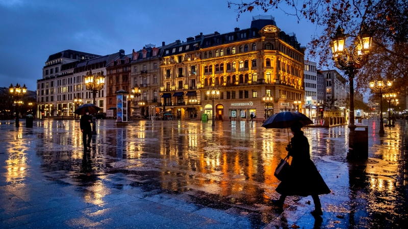 In this Jan. 22, 2021, file photo, people under umbrellas on the square in front of the Old Opera in Frankfurt, Germany, on a rainy. (AP Photo/Michael Probst, File)
