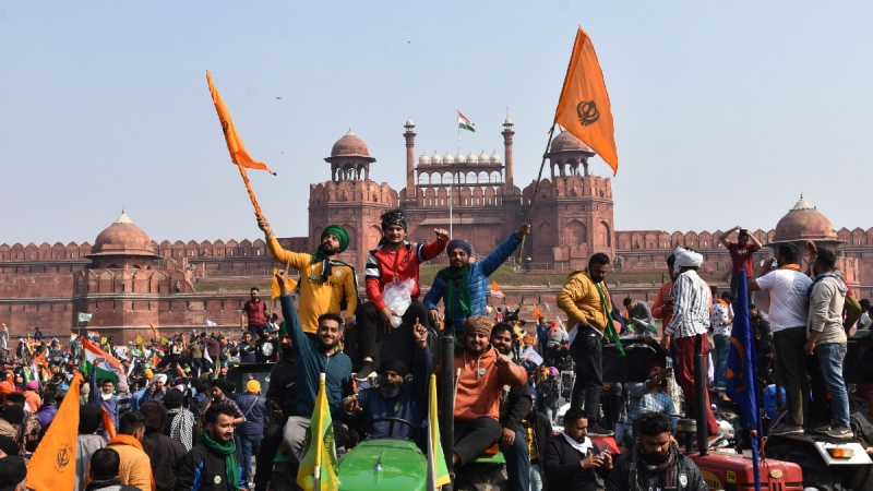 Sikhs wave the Nishan Sahib, a Sikh religious flag, as they arrive at the historic Red Fort monument in New Delhi, India, on Jan. 26, 2021. (Dinesh Joshi / AP)