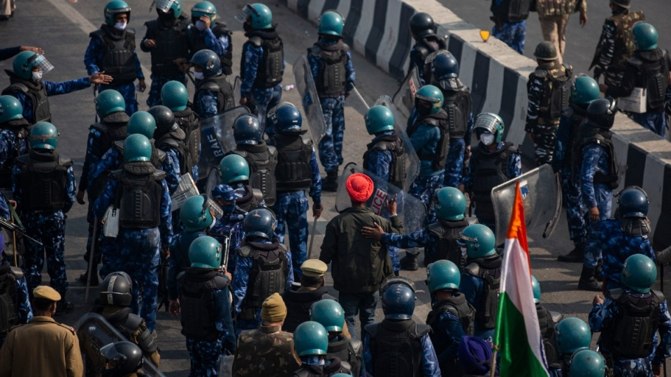 A protesting farmer surrounded by police