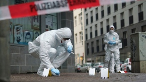Officers of the forensics department secure traces of blood on a sidewalk in Frankfurt, Germany, on Jan. 26, 2021. (Frank Rumpenhorst / dpa via AP)