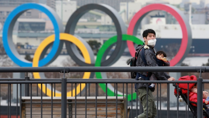 Walking on the Odaiba waterfront with Olympic rings seen in the background in Tokyo, on Jan. 26, 2021. (Koji Sasahara / AP)