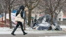 FILE - A pedestrian walks past a snow covered tent encampment in Trinity Bellwoods park in Toronto on Sunday November 22, 2020. THE CANADIAN PRESS/Frank Gunn