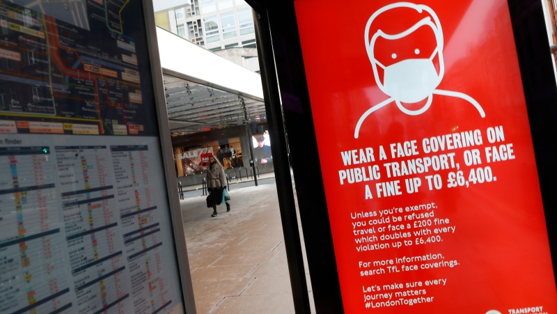 A digital display on a bus stop tells passengers that it is mandatory to wear a mask to prevent the spread of COVID-19 on public transport in London, Tuesday, Jan. 26, 2021. (AP Photo/Alastair Grant)