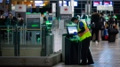 A worker cleans a check-in kiosk in the domestic terminal at Vancouver International Airport, in Richmond, B.C., on Thursday, January 21, 2021. THE CANADIAN PRESS/Darryl Dyck