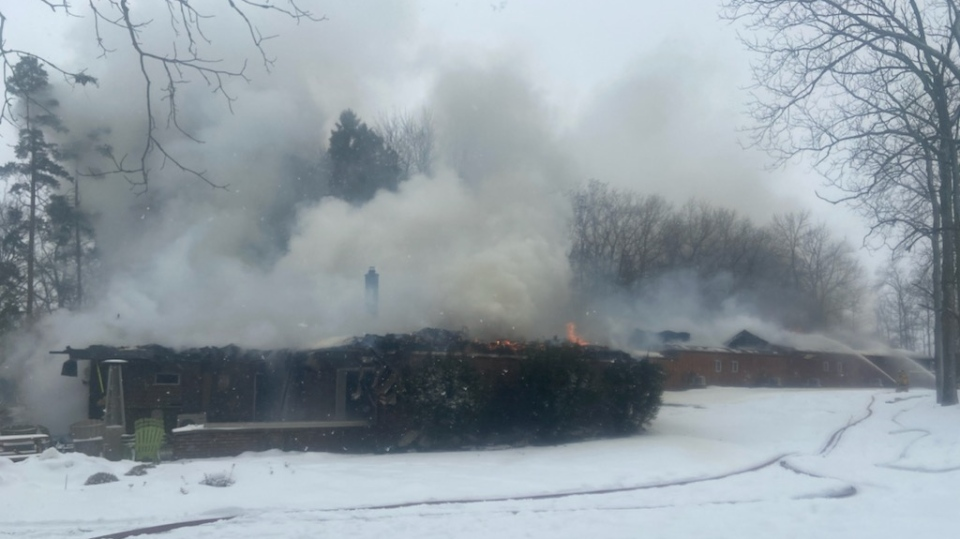 A motel near Stratford seen smoking as crews battle a fire. (@OPP_WR / Twitter)