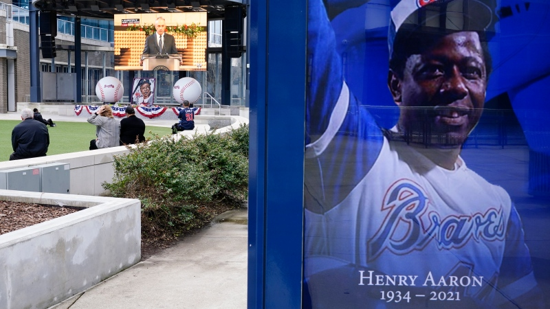 Hank Aaron signage is seen as people watch a memorial at Truist Park, home of the Atlanta Braves, to attend the memorial for Baseball Hall of Famer and Braves legend Hank Aaron, Tuesday, Jan. 26, 2021, in Atlanta. Just 2 1/2 weeks before his death Friday, Han 22, 2021, at age 86, Aaron joined civil rights icons to receive the COVID-19 vaccine. He wanted to spread the word to the Black community that the shots were safe in the midst of a devastating pandemic. (AP Photo/Brynn Anderson)
