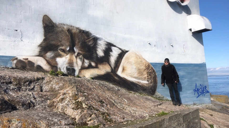 Paul Archer signed a larger-than-life mural of Staqeya that he painted on the side of a building on the small island in late June 2020. (CTV News)