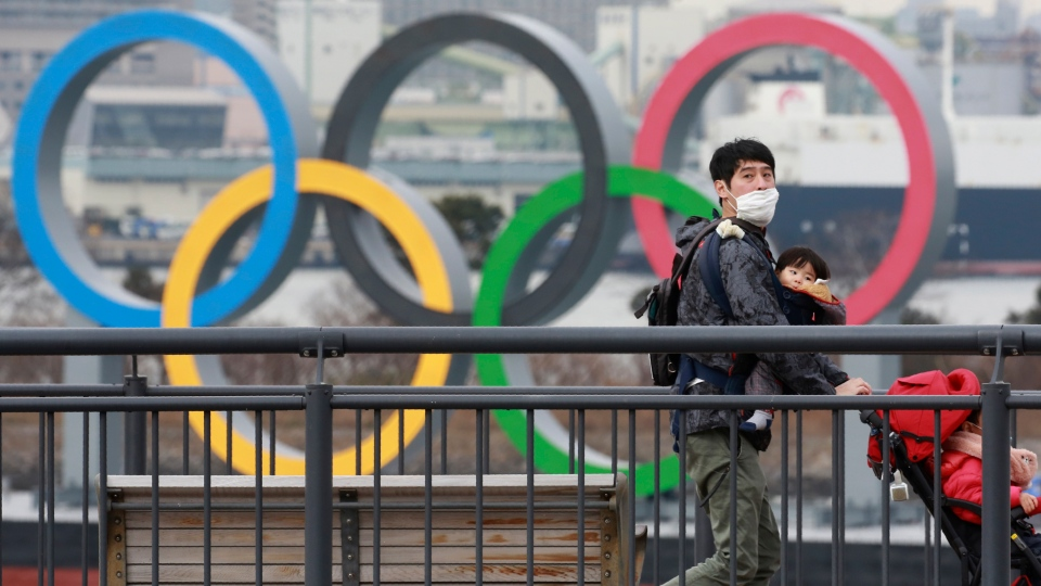 People wearing face masks to protect against the spread of the coronavirus walk on the Odaiba waterfront as Olympic rings is seen in the background in Tokyo, Tuesday, Jan. 26, 2021. (AP Photo/Koji Sasahara)