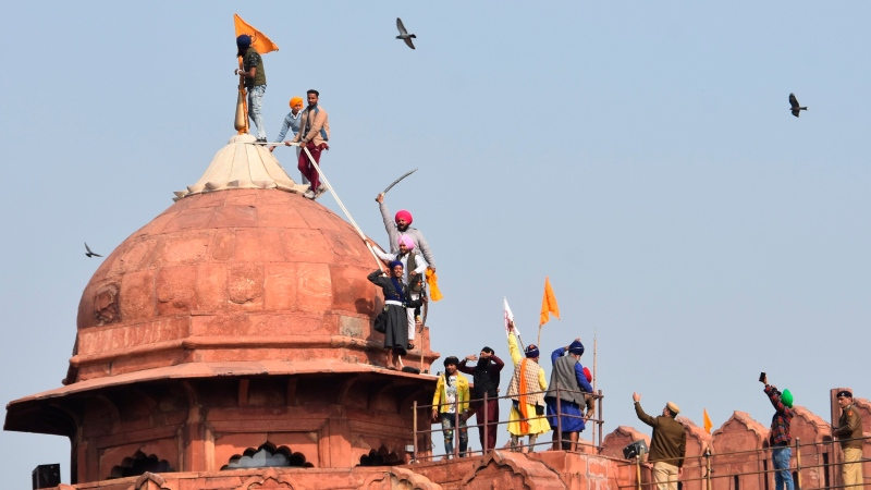 Sikhs hoist a Nishan Sahib, a Sikh religious flag, on a minaret of the historic Red Fort monument in New Delhi, India, Tuesday, Jan. 26, 2021. (AP Photo/Dinesh Joshi)