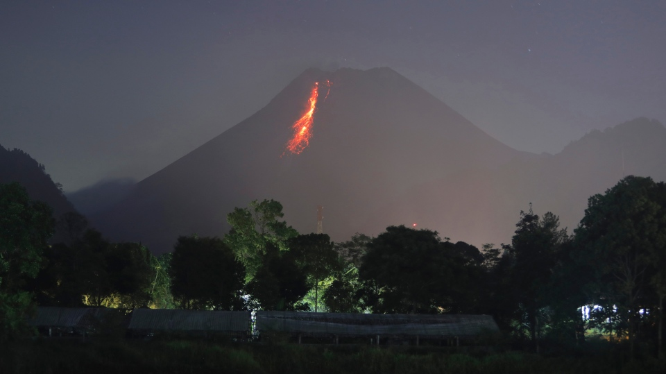 In this time-lapsed photo, hot lava runs down from Mount Merapi as its activity continues since local geological authority raised the alert level to the second-highest level in November, in Kaliurang, Indonesia, early Sunday, Jan. 24, 2021. (AP Photo/Trisnadi)