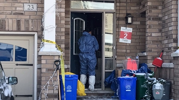 Police in blue attire and masks enter a home on Clifford Crescent in Tottenham on Wed., Jan. 27, 2021, after the body of a woman was found inside. (Rob Cooper/CTV News)