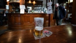 A half-full beer glass remains on a table at the Dispensary pub in Liverpool, England, Monday Oct 12, 2020. (AP Photo/Jon Super)